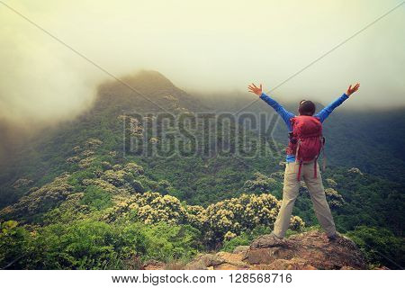 cheering young woman hiker open arms outdoor
