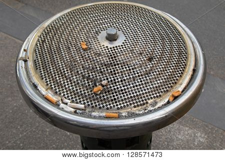 Extinguished cigarette butts on top of public cigarette stubs, ashtray bin, provided at the park in Melbourne, Australia