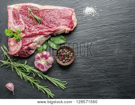 Raw beef steaks with spices on the black cutting board.