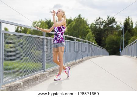 Beautiful and slim blonde woman drinks water and taking a break after stamina training. Standing on a bridge.