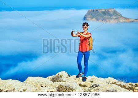 female traveler with backpack  standing on the trail against sea and blue sky at early morning. Balos beach on background, Crete, Greece. Woman taking a photo in smartphone
