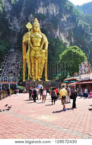 KUALA LUMPUR, MALAYSIA - SEMPTEMBER 1, 2014: Tourists in front of the Lord Murugan statue in Batu Caves temple. Batu Caves temple is a sacred place for the Hindu's in Malaysia.