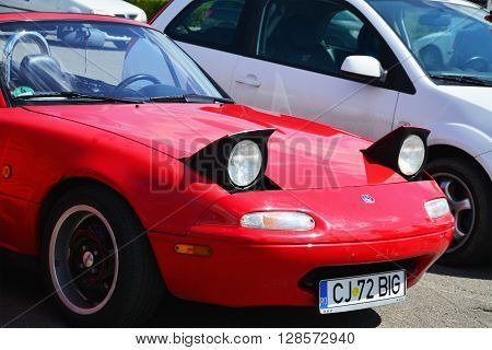 CLUJ-NAPOCA ROMANIA - APRIL 16 2016: Classic red Mazda MX-5 NA Series I (Mazda Miata) two-seat convertible roadster with retractable headlamps at the 2016 Retro Spring Parade.