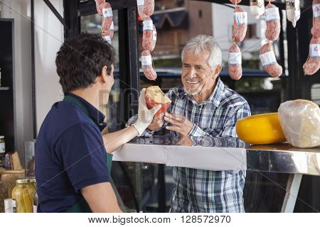 Man Buying Cheese From Salesman In Shop