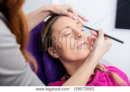 Woman Having Her Makeup Applied In Salon