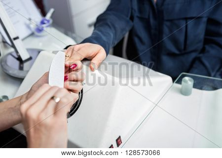 Manicurist Performing Manicure On Client's Hand At Beauty Parlor