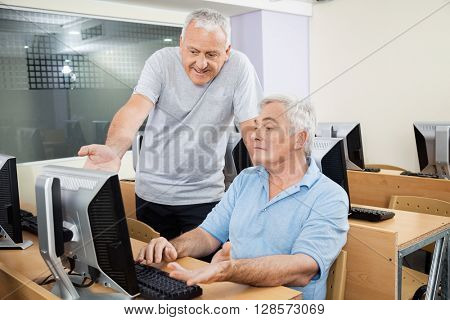 Senior Man Helping Male Classmate In Using Computer