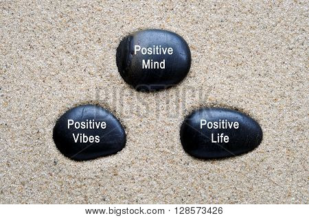 Positive mind, positive vibes, positive life quotes on zen stones with sand background.