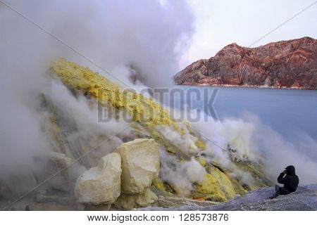 Kawah Ijen volcano, Java island, Indonesia: Person in sunrise in the crater of an active Ijen volcano with clouds of smoke close to the world's largest acid lake