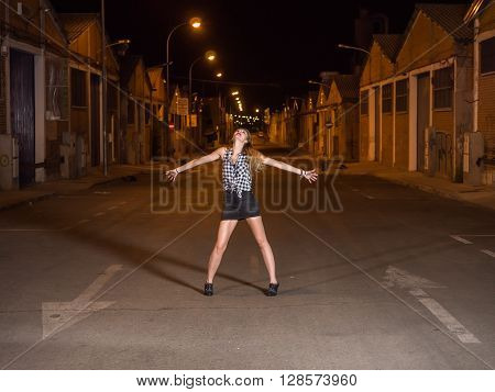 pretty blonde standing with legs and arms outstretched on the road