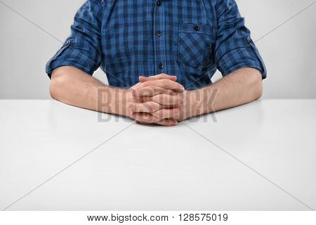 Cropped portrait of a man sitting with his clasped hands. Symbols and gestures. Body language. Hand gesture. Readiness for work. Listen attentively. Straight posture.