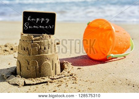 closeup of a sandcastle on the sand of a beach topped with a black signboard with the text happy summer written in it, and an orange beach pail next to it
