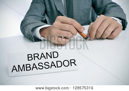 closeup of a young caucasian man wearing a gray suit sitting at his office desk, with a name plate in front of him with the text brand ambassador written in it