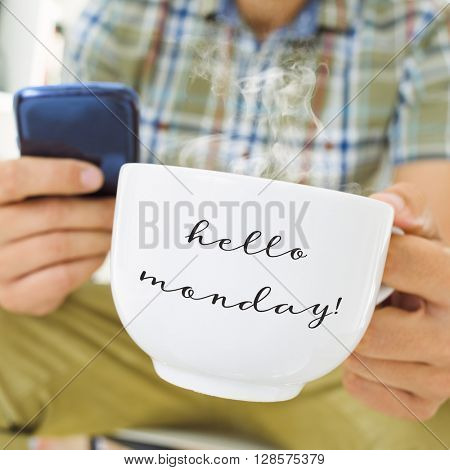 closeup of a young man using a smartphone with a cup of coffee or tea in his hand with the text hello monday written in it