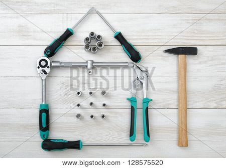 Top view of different type of constructive tools making shape of home, house. Construction instruments and tools. Set of tools. Compact tool box. Mend and repair. Home tool kit.