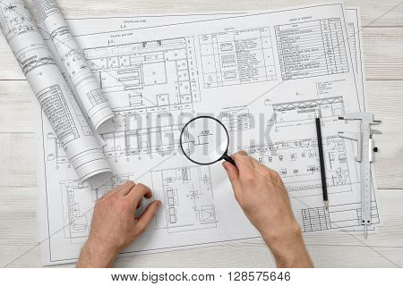 Close-up hands of architect while working process with magnifying glass. Top view composition. Workplace of architect. Engineering work. Construction and architecture. Architect drawing.  Research and investigation. Deep scan.