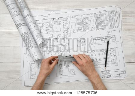 Hands of architect holding a centimeter device over drawing layout in top view. Workplace of architect or constructor.. Engineering work. Construction and architecture. Architect drawing. Measurement.