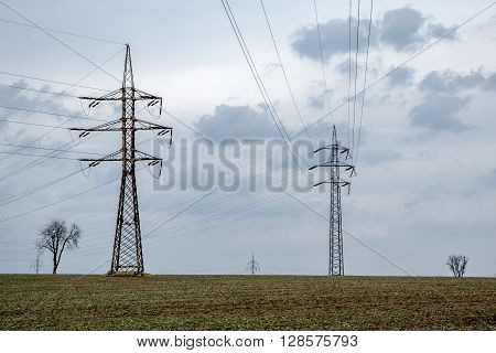 Electricity pylons with a blue cloudy sky