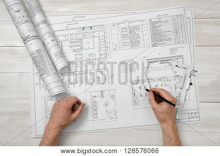 Hands of man holding a pencil over drawing layout in top view.  Workplace of architect or constructor. Engineering work. Construction and architecture. Architect drawing. Exact calculation.