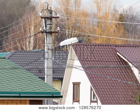 electrical wires support with electricity cables in the background of cottage building insulated houses made of red brick and siding with light brown roofs