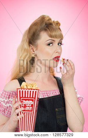 Pin up girl eating from a carton of popcorn