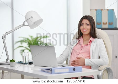 Pregnant woman sitting at her workplace in the office