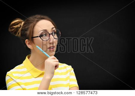 Attractive young blond girl  in glasses against blackboard.