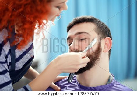Professional hairdresser shaving beard with razor