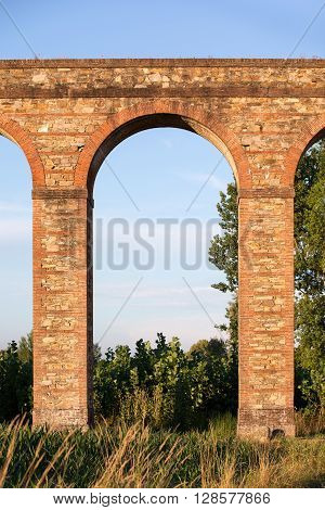 Arch section of the Nottolini Aqueduct in Tuscany near Lucca Italy. Warm evening light with classic Tuscan textures and tones. Concepts could include Travel Architecture Europe others.
