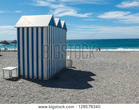 Sunny beach with changing rooms against of endless sea. La herradura Granada Andalusia Spain