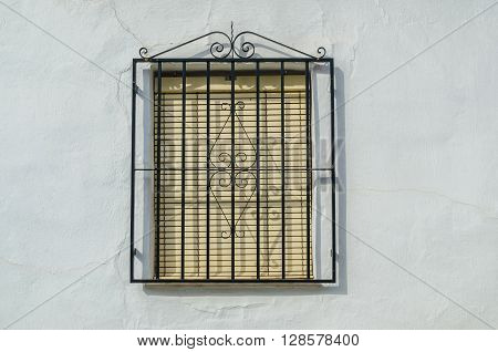 Shuttered window on white wall with black decorative railings. Frigiliana Granada Andalusia Spain