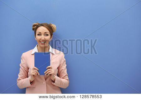 Attractive young blond girl  against light blue wall.