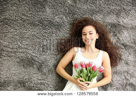 Young woman with tulips lying on the floor