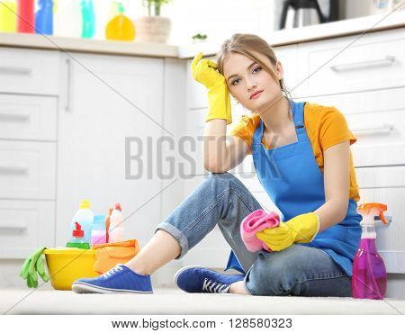 Cleaning concept. Young woman sitting on the floor with cleaning fluids