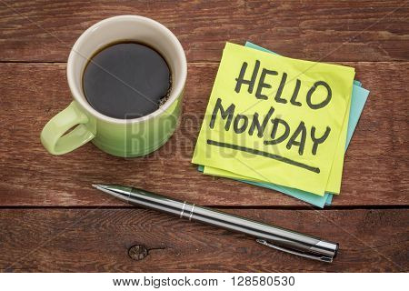 Hello Monday cheerful handwriting on sticky note with cup of coffee