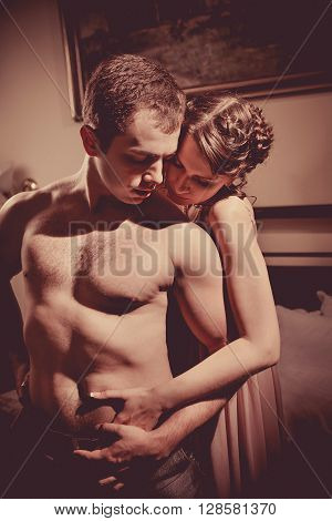 Beautiful Couple Is Undressing In The Bedroom. Retro Styled Toning.