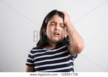indian small girl with headache, asian cute girl having headache, indian small girl stressed and sad because of head ache