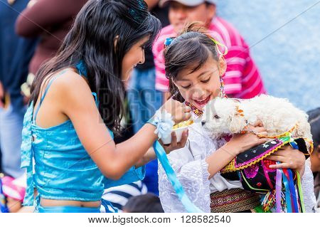 Banos De Agua Santa - 29 November, 2014 : Two Youth Girls Dressed In Ecuadorian Folk Costumes Feeding A Puppy On The Street In Banos De Agua Santa On November 29, 0142