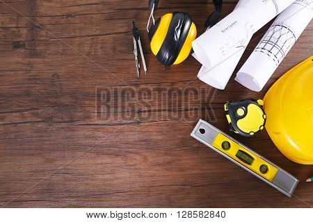 Construction blueprints with tools and helmet on wooden table, top view