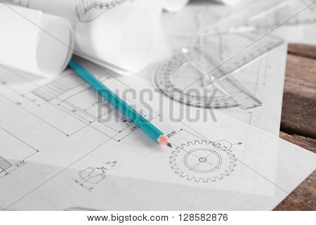 Set of engineering drawings with tools on wooden table closeup