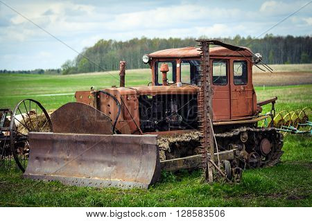Old rusty crawler tractor with shovel on a green field