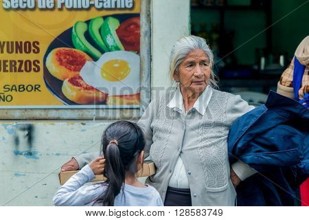 Banos De Agua Santa - 29 November, 2014: Hispanic Grandmother Buying A Pizza For Her Granddaughter On The Streets Of South America In Banos De Agua Santa On November 29, 2014