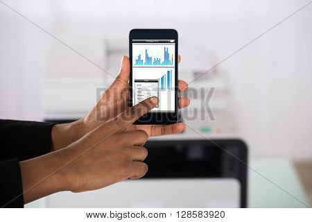 Close-up Of Businesswoman Hand Using Smartphone For Printing Graph Paper