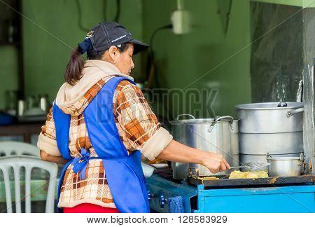 Banos De Agua Santa - 29 November 2014: Latin Woman Cooking On The Streets Of Banos De Agua Santa Ecuador In Banos De Agua Santa On November 29 2014
