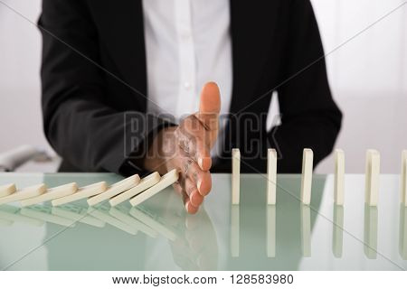 Close-up Of Businesswoman Hand Stopping Dominoes From Falling On Office Desk