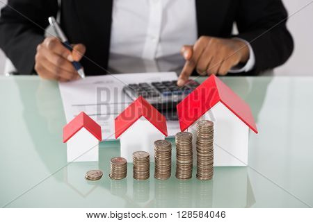 Close-up Of Businesswoman Calculating Invoice With Stacked Coins And House Models On Desk