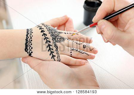 Henna ornaments on girl's hand closeup