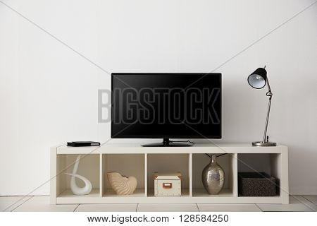 wide screen TV on white stand near light wall