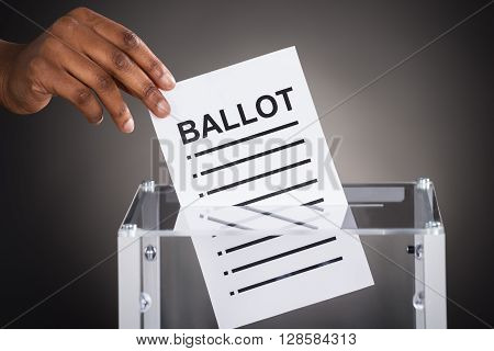 Close-up Of A Person Hand Inserting Ballot In Glass Box Against Gray Background