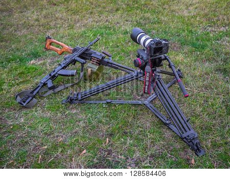 Odessa, Ukraine - December 02, 2015: The camera Canon and two machine guns lying on the grass. War correspondent concept.